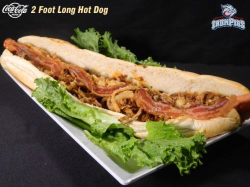 "The ""Hog Dawg"" featuring a Two Foot All Meat Hot Dog, Topped with Chili, Beer Cheese, Bacon, and Onion Straws, served on a Fresh French Bread Bun and cut into Four Pieces, Lehigh Valley IronPigs grapic"