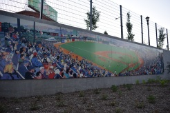 A mural of old MIdway Stadium adorns a wall along the covered concourse.