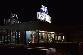 A night view of the big CHS Field sign and Saints Team Store from outside the stadium.
